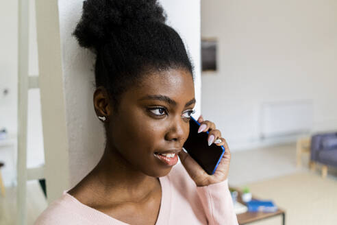 Woman looking away while talking on mobile phone standing at home - GIOF10782