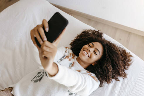 Smiling woman using mobile phone while lying on bed at home - TCEF01471