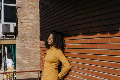 Smiling woman with hands behind back leaning on wall - TCEF01483