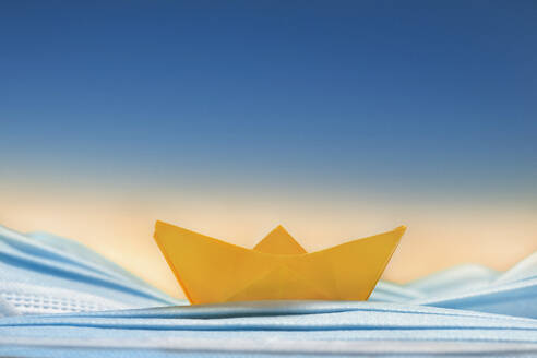 Yellow origami boat on blue disposable face mask - FSIF05606