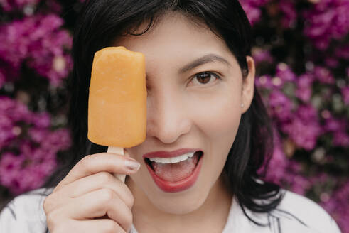 Happy woman with mouth open covering eye with orange ice cream - DSIF00269