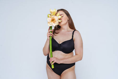 Young woman wearing black bikini smelling flowers against white background - OIPF00100