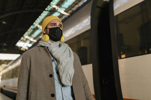 Man with protective face mask and headphones looking away while standing by train at station - EGAF01532