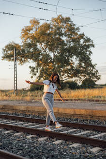 Carefree young woman with arms outstretched walking on railroad track during sunset - JRVF00180