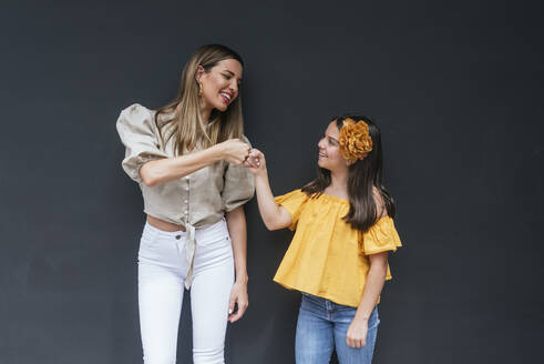 Cheerful mother and daughter giving fist bump while standing against black background - DSIF00300