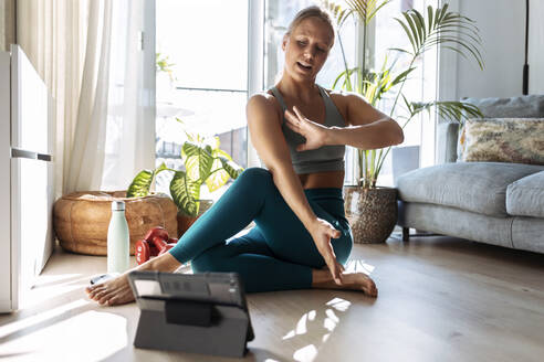Young woman doing yoga while learning from digital tablet sitting at home - JSRF01273