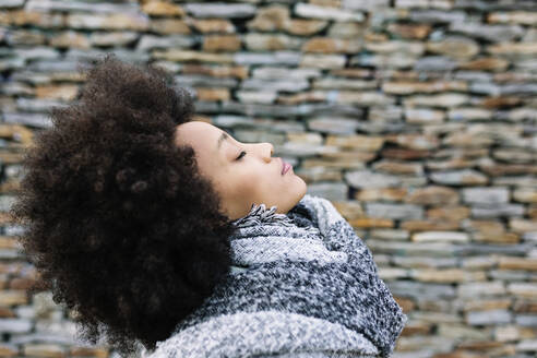 Young woman with eyes closed in warm clothing by stone wall - XLGF01037