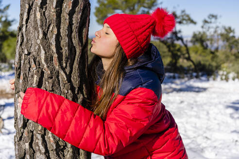 Woman wearing red knit hat kissing while hugging tree in forest - DLTSF01563