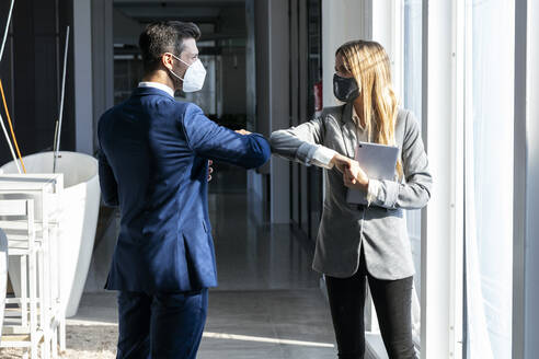 Businessman giving elbow bump to colleague while standing in office during COVID-19 - JSRF01293