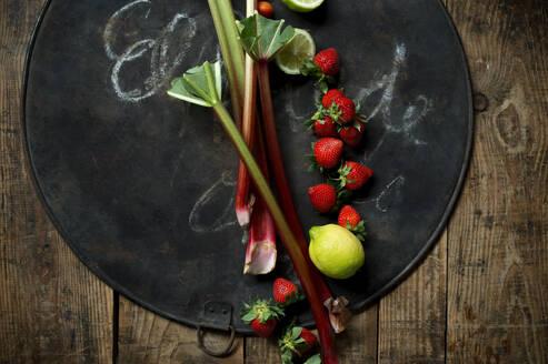 Fresh rhubarb, strawberries, lemon and lime on rustic baking sheet - ASF06690