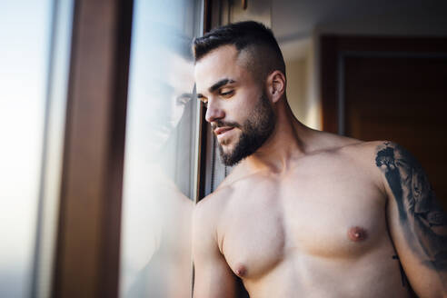 Bearded shirtless man contemplating while looking through window in living room - MIMFF00528