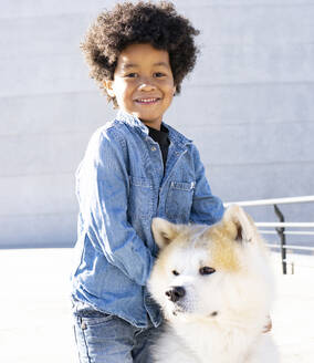 Boy with arm around dog smiling while standing outdoors - JCCMF00974