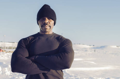 Muscular build sportsman wearing knit hat standing with arms crossed in snow during sunny day - JCCMF01004