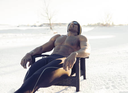Athlete wearing sunglasses sitting while relaxing on chair in snow - JCCMF01013