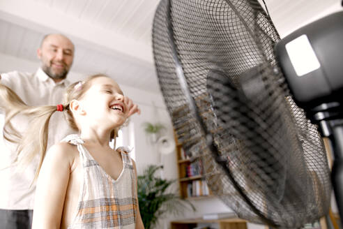 Girl in front of electric fan while father standing at home - KMKF01480