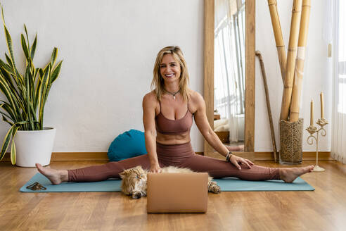 Smiling mature woman with laptop stroking cat while stretching on mat at home - DLTSF01606