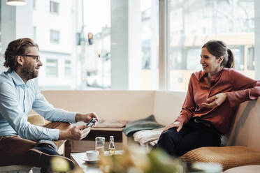 Male entrepreneur discussing with female colleague at coffee shop - JOSEF03185