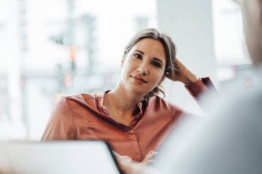 Female professional with hand in hair during meeting at coffee shop - JOSEF03197