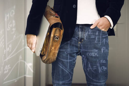 Mature male professional with hand in pocket, laptop and bag - UKOF00114