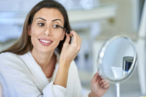 Smiling woman applying mascara while looking in mirror at home - KIJF03526