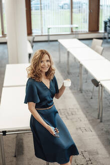 Smiling businesswoman with coffee cup in board room - JOSEF03272