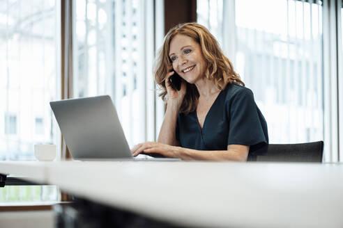 Smiling female entrepreneur working on laptop while talking over smart phone at board room - JOSEF03278