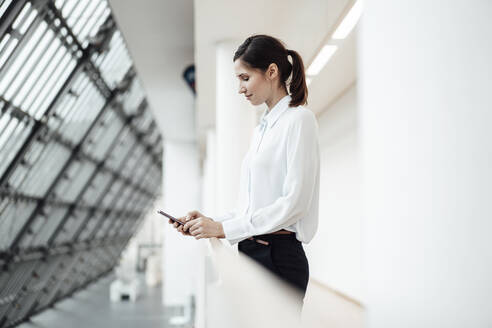 Female entrepreneur text messaging on smart phone in office corridor - JOSEF03311