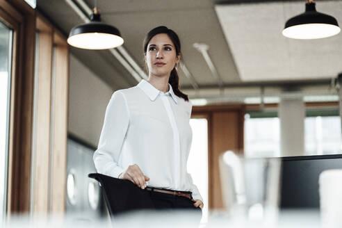 Confident female entrepreneur standing in illuminated office - JOSEF03395