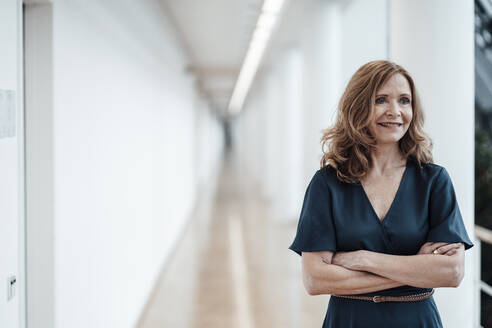 Confident businesswoman with arms crossed looking away at corridor - JOSEF03428