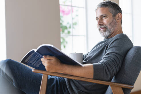 Mature businessman with coffee cup and book looking away while sitting at home - SBOF02589