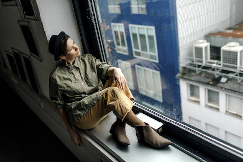 Fashionable woman looking through window while sitting on window sill at studio - OGF00793