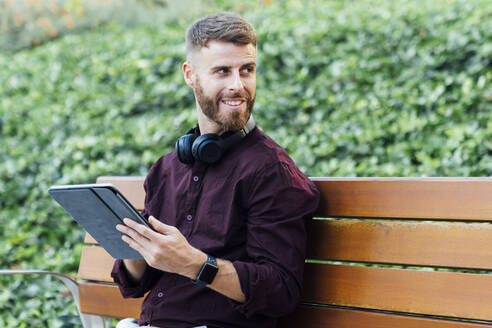 Businessman with digital tablet and headphones looking away while sitting at park - BOYF01651