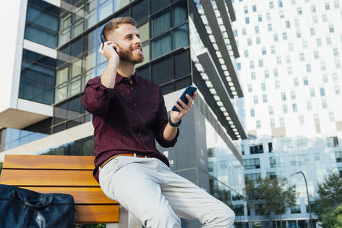 Businessman with smart phone smiling while adjusting headphones sitting in city - BOYF01663