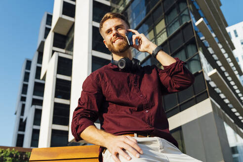 Businessman looking away while talking on mobile phone sitting on bench - BOYF01669