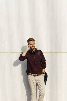 Smiling businessman with shoulder bag talking on mobile phone while standing against white wall - BOYF01681
