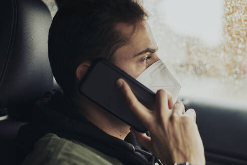 Young man talking through mobile phone while sitting in car during COVID-19 - ACPF01084