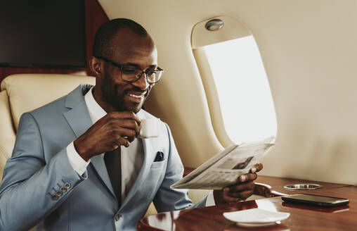 Smiling businessman reading newspaper while having coffee in airplane - OIPF00264