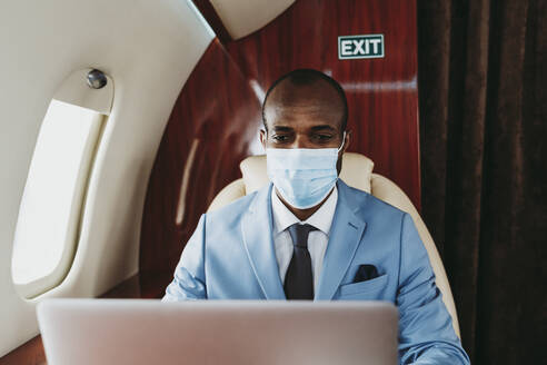 Young businessman working on laptop in airplane during pandemic - OIPF00294
