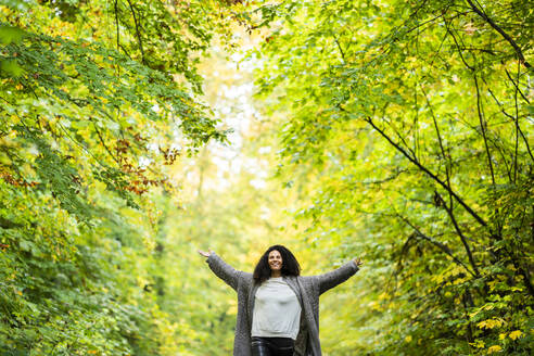 Smiling woman with arms outstretched in forest - AKLF00002