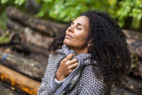 Curly hair woman smiling while sitting with eyes closed in forest - AKLF00005