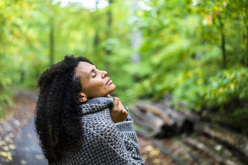 Mid adult woman wearing jacket sitting with eyes closed in forest - AKLF00011