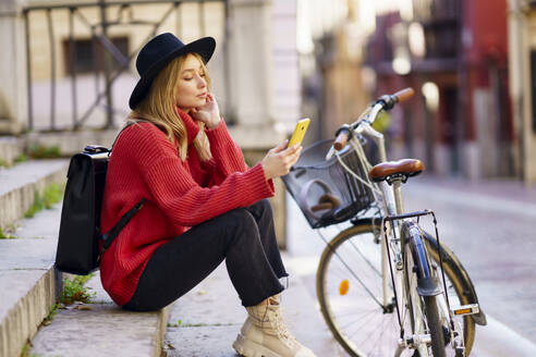 Young woman wearing hat using mobile phone while sitting by bicycle on steps - JSMF01951