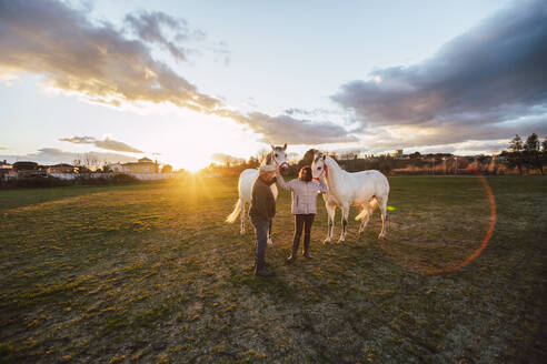 Ranchers talking while standing with horses in ranch during sunset - RSGF00525