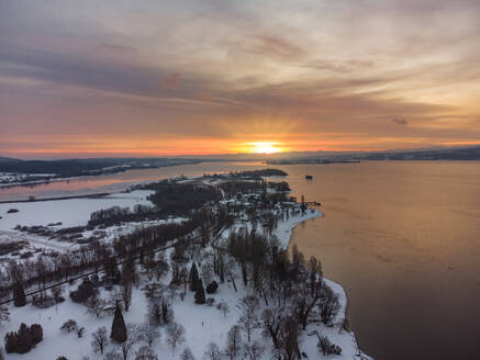 Germany, Baden-Wurttemberg, Radolfzell, Aerial view of snow-covered Mettnau peninsula at sunset - ELF02349