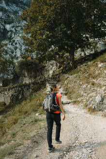 Hiker wearing backpack looking away while walking on Cares Trail at Picos De Europe National Park, Asturias, Spain - DMGF00437