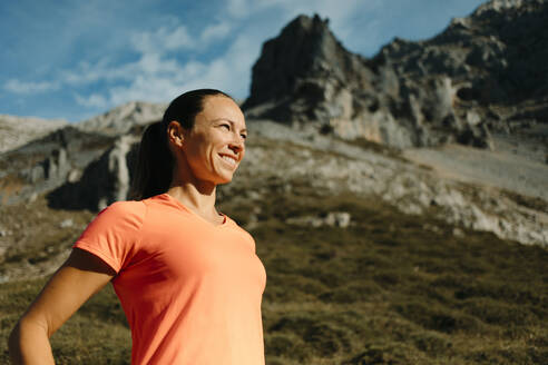 Female explorer smiling while standing against mountain at Cares Trail in Picos De Europe National Park, Asturias, Spain - DMGF00446