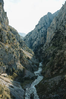 Scenic view of river flowing through mountains at Cares Trail in Picos De Europe National Park, Asturias, Spain - DMGF00467