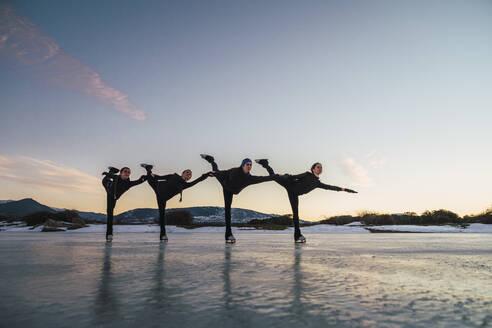Female figure skaters practicing on frozen lake at dusk - RSGF00532
