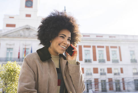 Smiling woman talking on mobile phone while standing in city - JCCMF01067