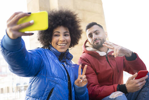 Friends gesturing peace sign while taking selfie  through mobile phone outdoors - JCCMF01091